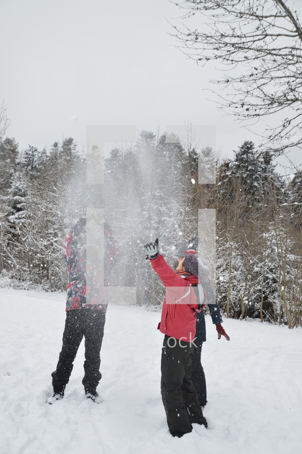 friends tossing snowballs into the air