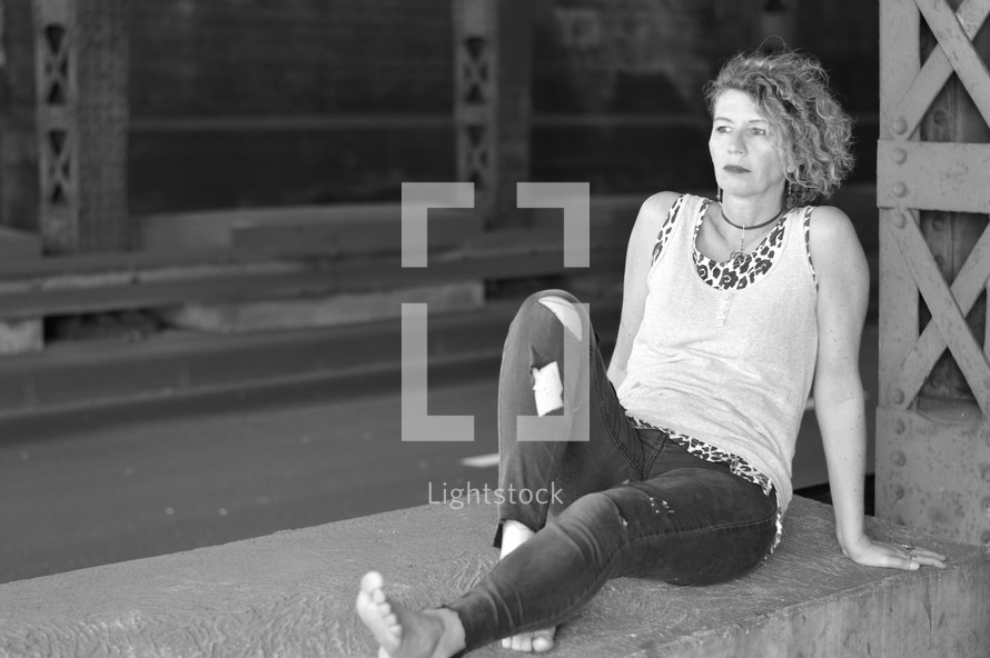 homeless woman sitting under a bridge
