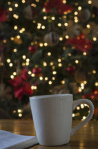 mug and open Bible on a coffee table and Christmas tree in the background