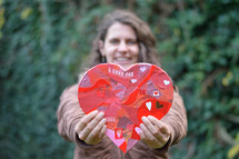 woman holding up a cutout paper heart