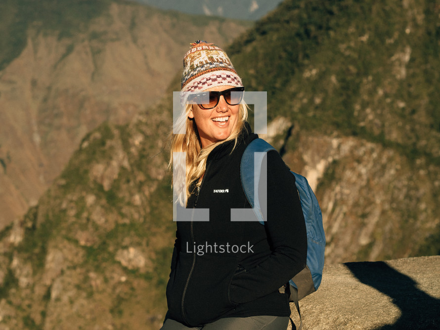 female hiker with a backpack, cap, and sunglasses