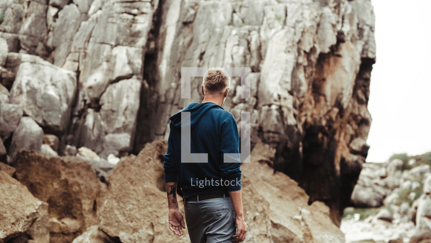 a man walking along a rocky shore
