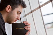 man praying by a window holding a Bible
