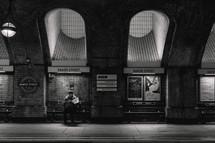 homeless man reading a newspaper at night