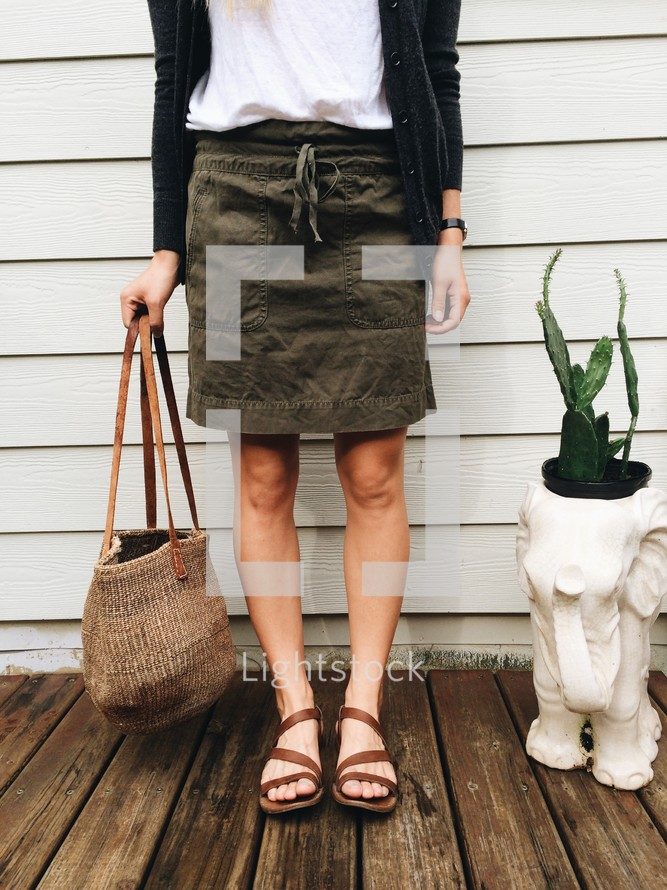 a woman standing holding a purse
