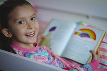 Girl in pajamas reading the Bible and smiling. She's reading the story of Noah before bedtime.  Reading a children's Bible.