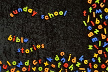 the words SUNDAY SCHOOL and BIBLE STORIES written with colorful magnetic letters on black ground