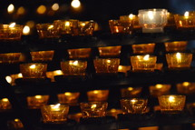 many lit candles in a dark church.  candle, lit, flame, fire, burning, candles, flames, kindled, light, lighted, blaze, blazing, burning, burn, many, much, lot, dark, lighten, brighten, bright, illuminate, illumine, shine, shining, see, seeing, show, showing, symbol, symbolic, symbolize, symbolizing, believe, believers, wax, church, pray, prayer, votive, darkness, burnt, donation, donate, ceremony, offering, offer, yellow, white, orange, row, line, lines, commemorate, remember, recall, remembrance, memory, memento, think of, sign, creed, rows, unlit