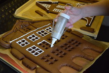 hand of a woman garnishing sugar icing at the window edges of a home made gingerbread house next to a breadboard with other gingerbread houses on it