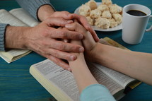 couple holding hands and praying over a Bible
