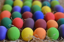 Colorfully painted Easter eggs on straw.