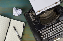 vintage typewriter with blank notebook, pen and crumbled ball of paper