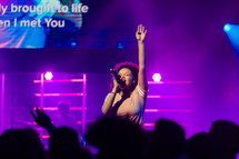 A woman singing on stage with her hand raised in worship.