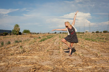 woman dancing in a freshly plowed corn field