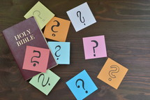 Holy Bible and question marks on sticky notes