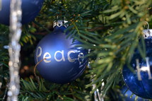The words Peace, Grace and Hope written in silver letters on blue Christmas ornament bulbs.