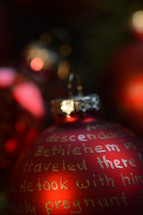 The Nativity story written in golden letters on red Christmas ornament bulbs.