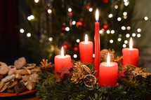 Five candles are burning at the Advent wreath for christmas day in front of a chrismas tree and next to a plate with christmas cookies