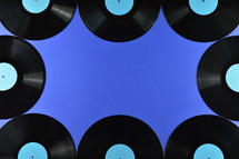 old black vinyl records with blank cyan labels on blue background as frame