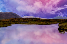 cotton candy clouds over a pond
