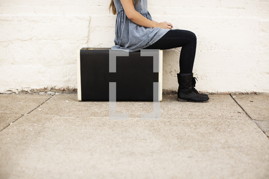 woman sitting on a suitcase turned to the side