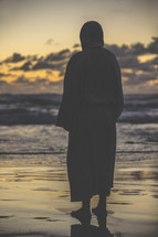 Jesus in a robe standing on a shore at sunset