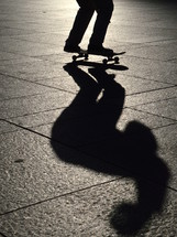 skater jumping on his skateboard with his shadow in evening backlight.