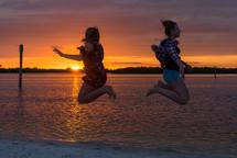 teen jumping on a beach at sunset
