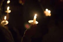 person holding a candle at a candlelight service
