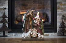 Nativity scene in front of a fireplace