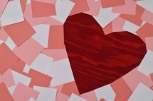 pile of blank rose, antique pink and white notepads showing a part of the red wooden background in the shape of a heart