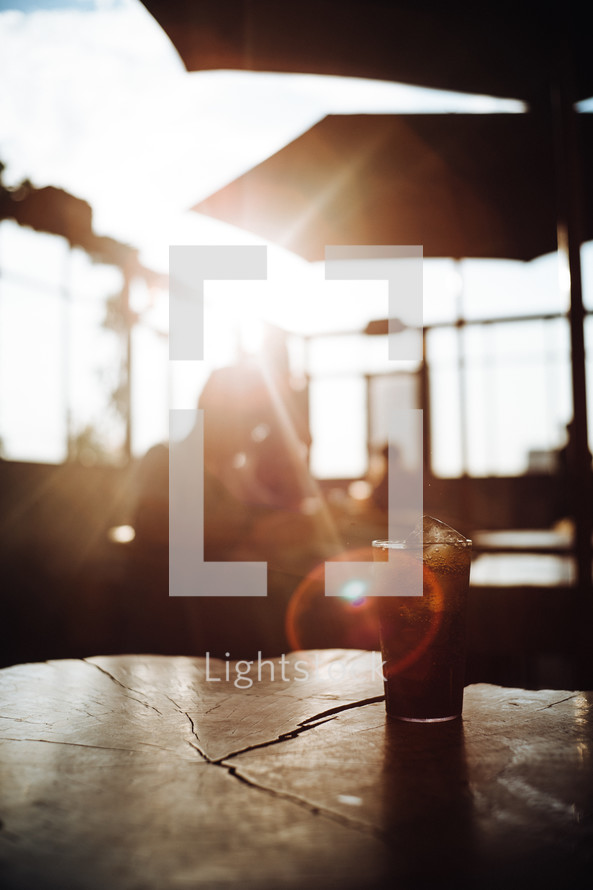 a glass of soda on a table in sunlight