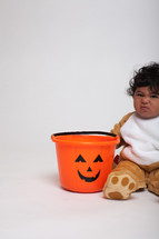 a toddler boy in a Halloween costume with a jack-o-lantern bucket