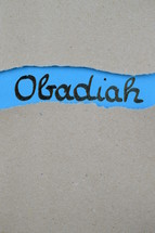 Obadiah - torn open kraft paper over blue paper with the name of the prophetic book Obadiah