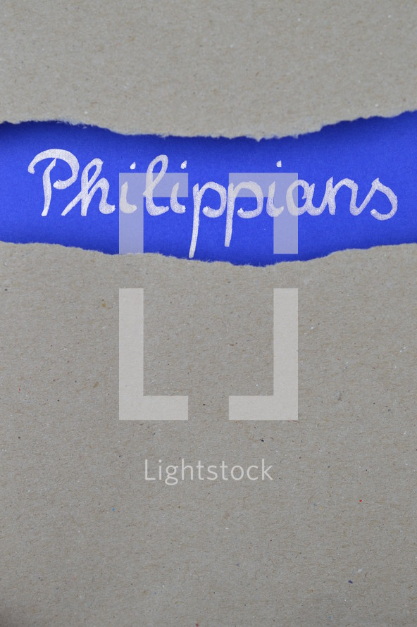 Philippians - torn open kraft paper over intense blue paper with the name of the letter from Paul to the Philippians