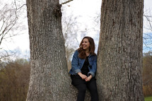 a woman sitting between two trees