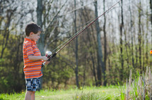 A boy holding a fishing pole at a pond on a sunny summer day.