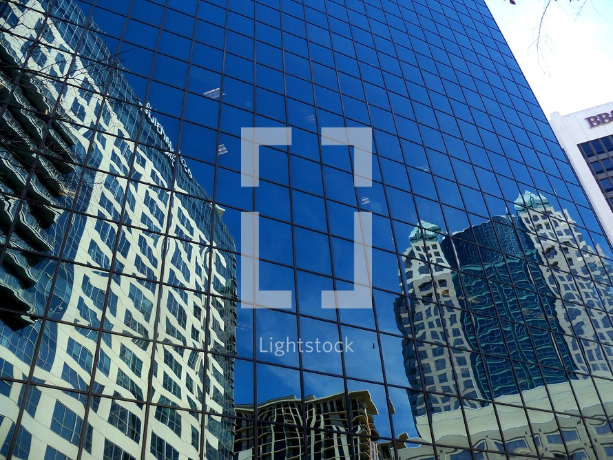 A glass building reflects the old and the  new buildings that stand side by side in a downtown city on a bright sunny day depicting commerce, business, corporate life and urban renewal city life.