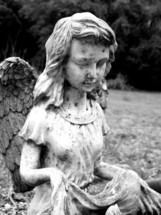 A statue of a female angel figure in a garden or graveyard setting. A black and white image of a female Angel weathered by storms, age, and life as a reminder that we have Gods angels looking over us as a constant reminder that this is not our permanent home.