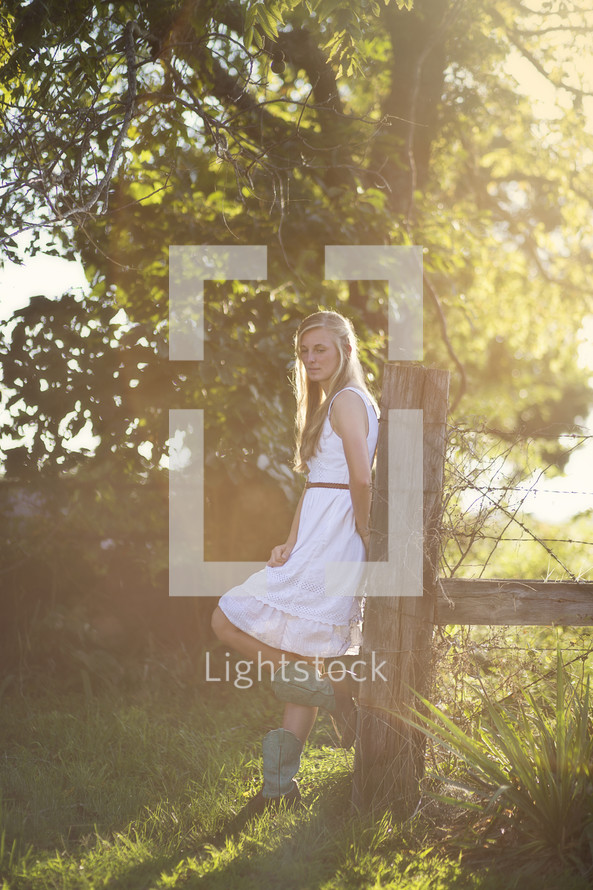 woman in cowboy boots leaning on a fence post