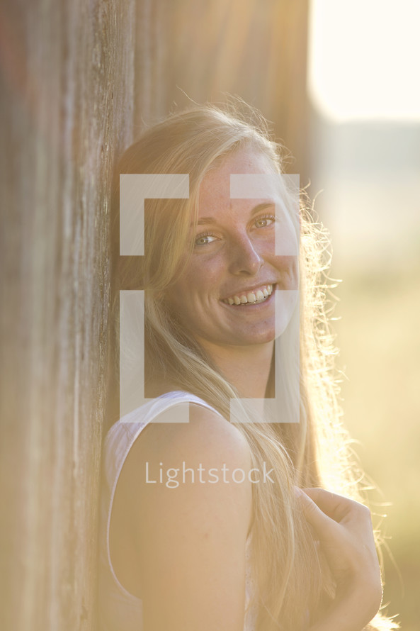 smiling woman leaning against a barn