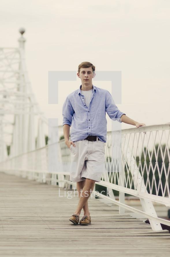 teen boy posing on a white bridge