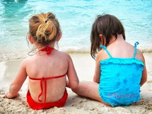 girls sitting on the beach in their bathing suits