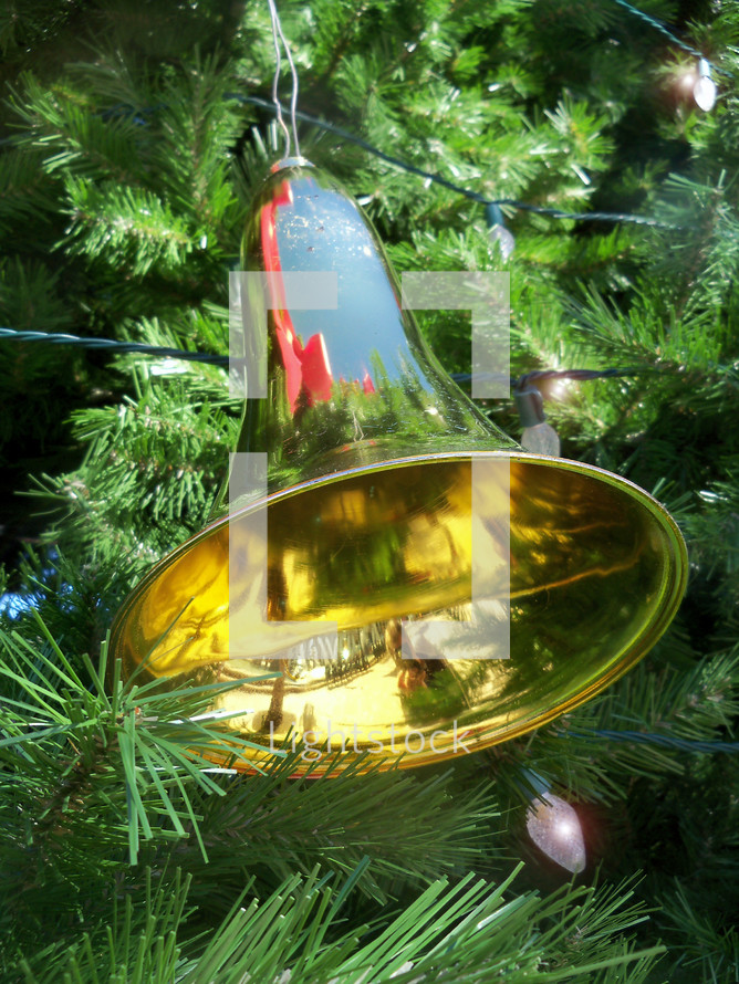 A brass Christmas bell decoration hanging on a Christmas tree reflecting the colors and glory of the Christmas season.