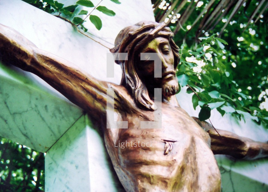 A statue of Jesus showing his wounds where He was pierced by a roman sword and nailed to the cross. This statue is made of bronze of Jesus on a marble cross bearing the sins of the world and taking the place of each of us on the cross.