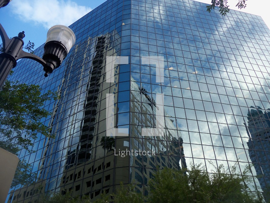 A City of glass reflection in downtown city showing the sky and reflecting cityscape surrounding its mirrored façade contrasting the old and the new corporate glass buildings with old architecture as cities grow and expand.
