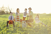 Family sitting on chairs in a meadow.