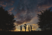 a silhouette of a family standing outdoors under an evening sky