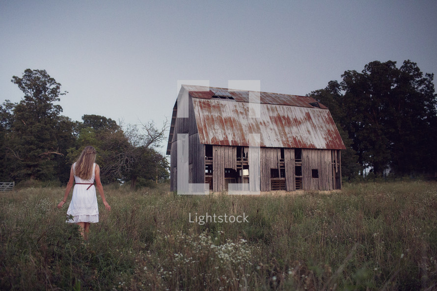 woman and an abandoned barn