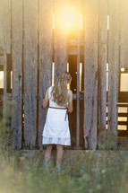 woman looking into an old weathered barn